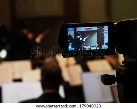 UKRAINE, LUGANSK - FEBRUARY 27,  2014: Lugansk Philharmonic Orchestra performed the Concerto No1 for piano and orchestra by Camille Saint-Saens. Conductor is Catherine Osadchaya, soloist - Irina Burgan.