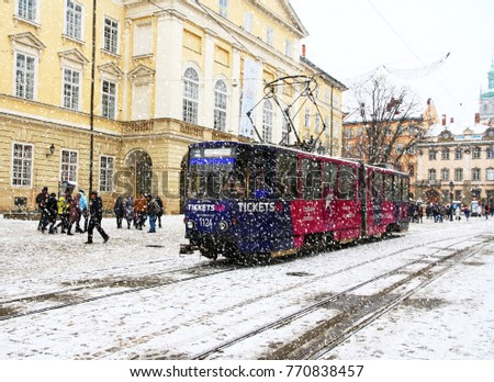 UKRAINE. LVIV - JANUARY 7, 2016: Old tram rides in the Market Square against the backdrop of historic architecture on a winter day.