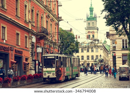 UKRAINE. LVIV - JUNE 20, 2015: Old tram rides through the market square against the backdrop of historic architecture.