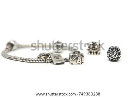 Ukraine, 11.04.2017: Pandora I love France. Heart, globe, kitties, journey, passport and suitcase. Silver beads and charms bracelets isolated on white background. Photo of Macro shot of jewelry.