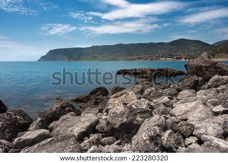 Ukraine, peninsula of Crimea, Sea coast on the Black Sea, large and small pebbles, large boulders, sea waves  - stock photo