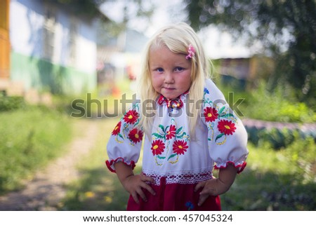 Ukraine, Perkalaba: August 15, 2015. The blond girl with blonde hair (a rarity for Ukrainian Hutsul highlanders) in national clothes with floral patterns walks around the house in the Carpathians