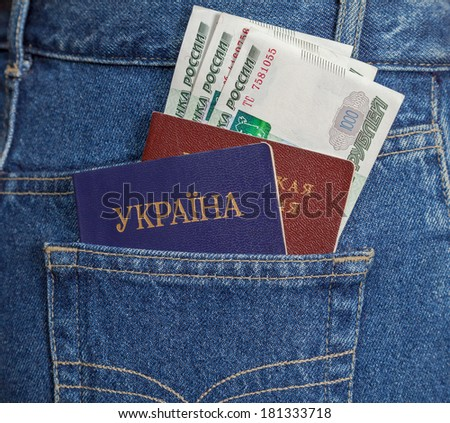 Ukrainian and Russian  passports in the back jeans pocket - stock photo