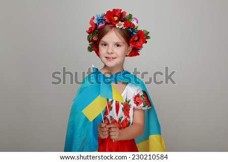 Ukrainian Beautiful little girl with a sweet smile, holding a big flag of Ukraine and is a fan of football competition, sports championships - stock photo