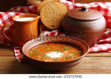 Ukrainian beetroot soup - borscht in bowl and pot, on napkin, on wooden background - stock photo