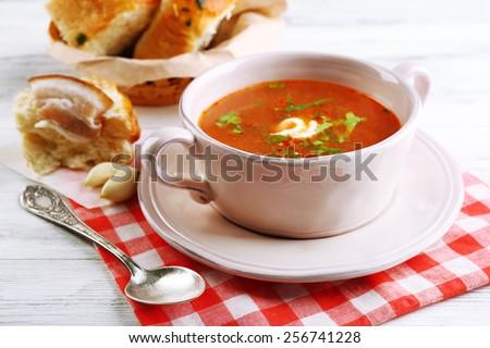 Ukrainian beetroot soup - borscht, on napkin, on wooden background - stock photo