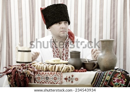 Ukrainian Cossack in national costume sitting at the table - stock photo