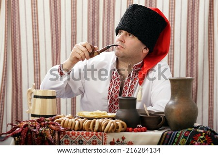 Ukrainian Cossack in Ukrainian national costume smoking pipe - stock photo