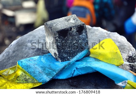 Ukrainian flag pressed to a stone with a piece of cobbles - stock photo