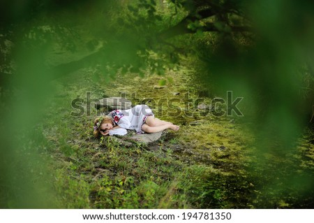 Ukrainian girl in national dress and a wreath of flowers on her head on a rock sleeping under a tree. In the background, a small stream flows - stock photo