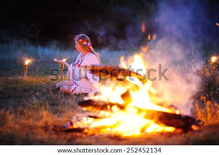 Ukrainian girl with a wreath of flowers on her head against a background of fire - stock photo
