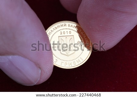 Ukrainian golden coins in hand - stock photo