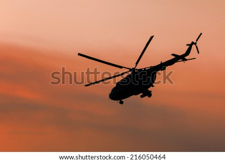 Ukrainian military helicopter in flight against a dramatic sunset after a combat mission - stock photo