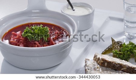 Ukrainian national red borscht soup served with a sour cream, salo sandwich and salty cucumbers decorated with parsley on white plate