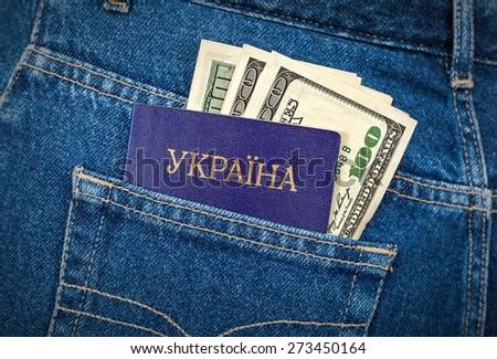 Ukrainian passport and dollar bills in the back jeans pocket - stock photo