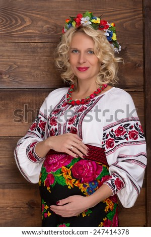 Ukrainian pregnant woman in traditional embroidered shirt - stock photo