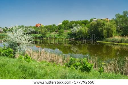 Ukrainian rural summer landscape with small river Sura in spring season. - stock photo