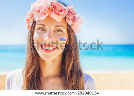 ukrainian woman wearing traditional wreath with the flag painted on her cheek - stock photo