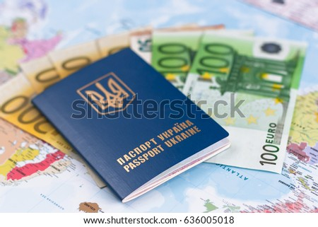 Ukranian travel passport laying  on different euro banknotes,  world map on the  background.