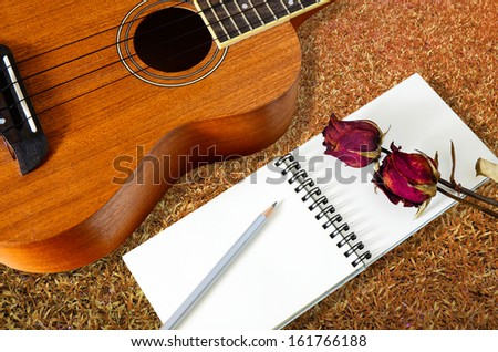 ukulele guitar with blank notebook and pencil - stock photo