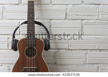 Ukulele on white brick background