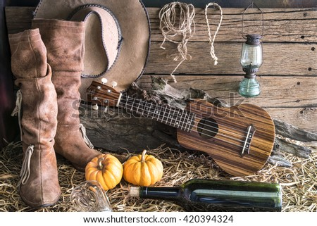 ukulele with american west rodeo brown cowboy hat and leather boots in vintage ranch barn studio background, Still life style - stock photo