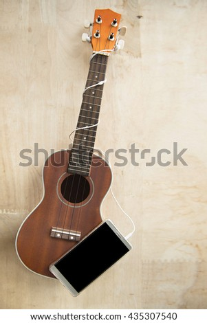 ukulele with phone on wood background
