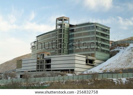 ULAANBAATAR, MONGOLIA - FEBRUARY 1: Building under construction with glass facade on February 1, 2015 in Ulaanbaatar. - stock photo