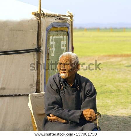 ULAN BATOR,MONGOLIA -APRIL 7.:Unidentified old man is resting before his yurt on April 7,2012 Mongolia.Most of the people in Mongolia are still wearing traditional clothing instead of western cloths.