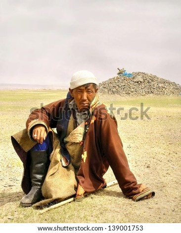 ULAN BATOR,MONGOLIA - APRIL 7; :Unidentified shepherd is resting during his work on the grass on April 7,2012 Mongolia. Most of the people in Mongolia are still wearing traditional clothing.