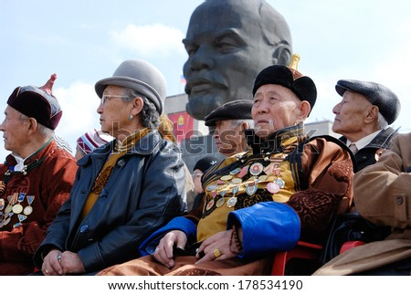 ULAN-UDE, RUSSIA - MAY 9, 2008: Elderly veterans of WWII sit at tribunes and watch the parade on annual Victory Day. Behind them there is a huge head of Lenin, a famous local monument.