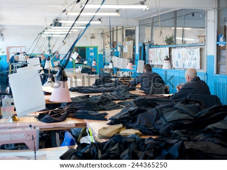 ULAN-UDE, RUSSIA - NOVEMBER 18, 2011: Unidentified men prisoners sew uniforms at a sewing workshop. To have job in modern Russian jail is luck as unemployment has come even there. - stock photo