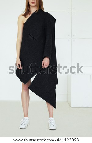 Ultra-fashion concept. Full length portrait of young fashionable woman with red hair wearing gray coat and posing over white background. Street style. Studio shot