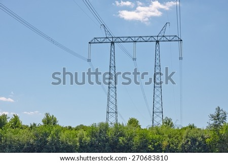 Ultra high voltage line crossing a river - stock photo