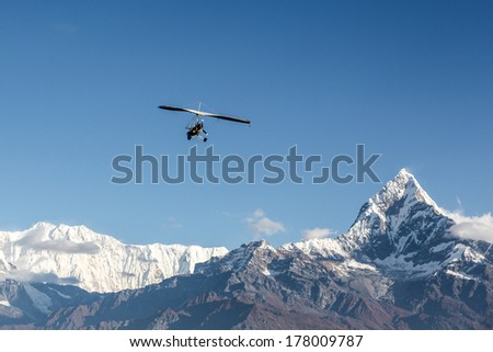 Ultra light plane flying over the Annapurna mountain range in the Himalayas near Pokhara, Nepal. The summit on the right is the Machapuchare (6993m), aka the fishtail mountain.