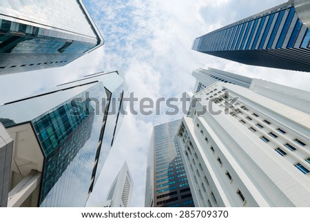 Ultra modern, sleek, highrise buildings, each with a unique architectural style, reaching up into a bright and cheerful, partly cloudy sky. - stock photo