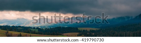 Ultra-wide panorama of Carpathian mountains. Dramatic stormy clouds over mountain range. Ukraine.