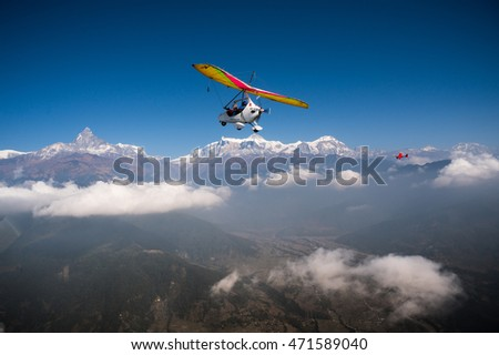 Ultralight trike and plane fly over Pokhara and Annapurna region. Machapuchare or fishtail and Himalayas on the background. Tourism in Nepal.