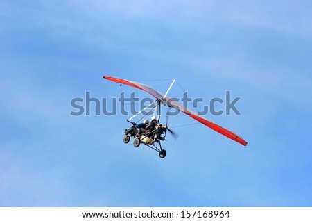 Ultralight trike flying with a pilot and a passenger