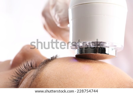 Ultrasound beauty treatment, The woman's face during a facial at a beauty salon  - stock photo