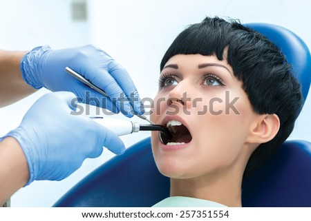 Ultraviolet procedure to seal. Dentist makes the process of treatment of a beautiful young girl. - stock photo
