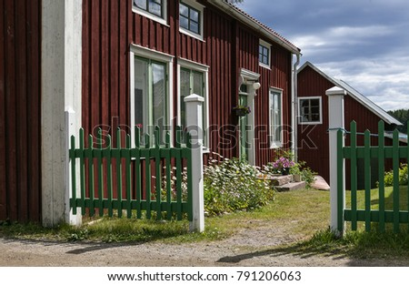 ULVON, SWEDEN ON JULY 18. Exterior of a red, white and green building, entry on July 18, 2017 in Ulvon, High Coast Heritage, Sweden. Gate, walls and vegetation.