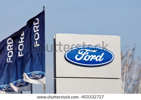Ulyanovsk, Russia - April 09, 2016: Ford sign and flags near Ford car selling and service center.