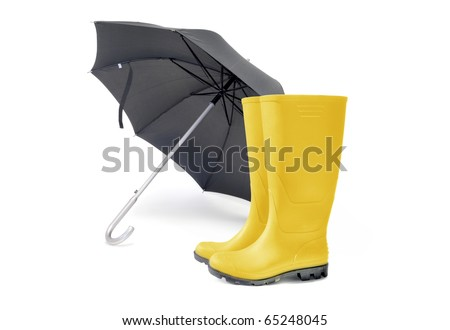 Umbrella and a pair of yellow wellington boots - stock photo