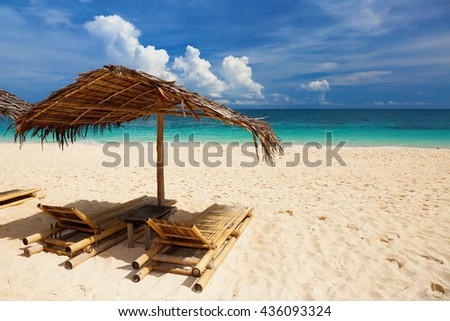 Umbrella and beach beds on white sand tropical beach. Summer vacation concept. - stock photo