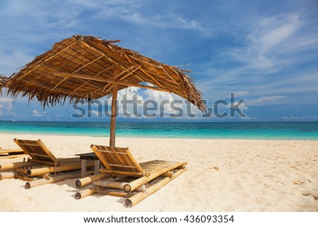 Umbrella and beach beds on white sand tropical beach. Summer vacation concept. Blue sea on the background.