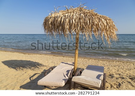 Umbrella and beach chairs on the beach - stock photo