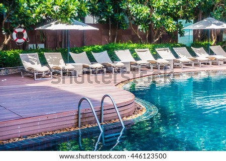 Umbrella and chair around beautiful luxury outdoor swimming pool in hotel resort