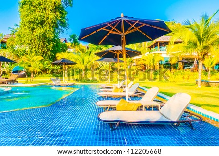 Umbrella and chair around beautiful luxury outdoor swimming pool in hotel resort - Boost up color Processing