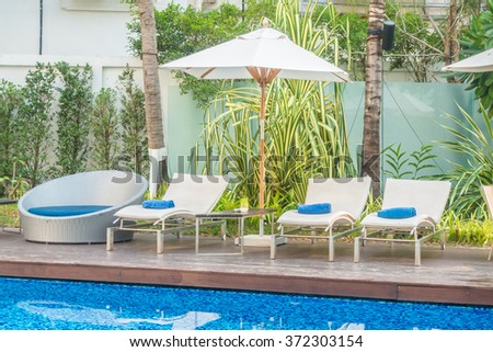 Umbrella and chair around beautiful luxury swimming pool in hotel resort
